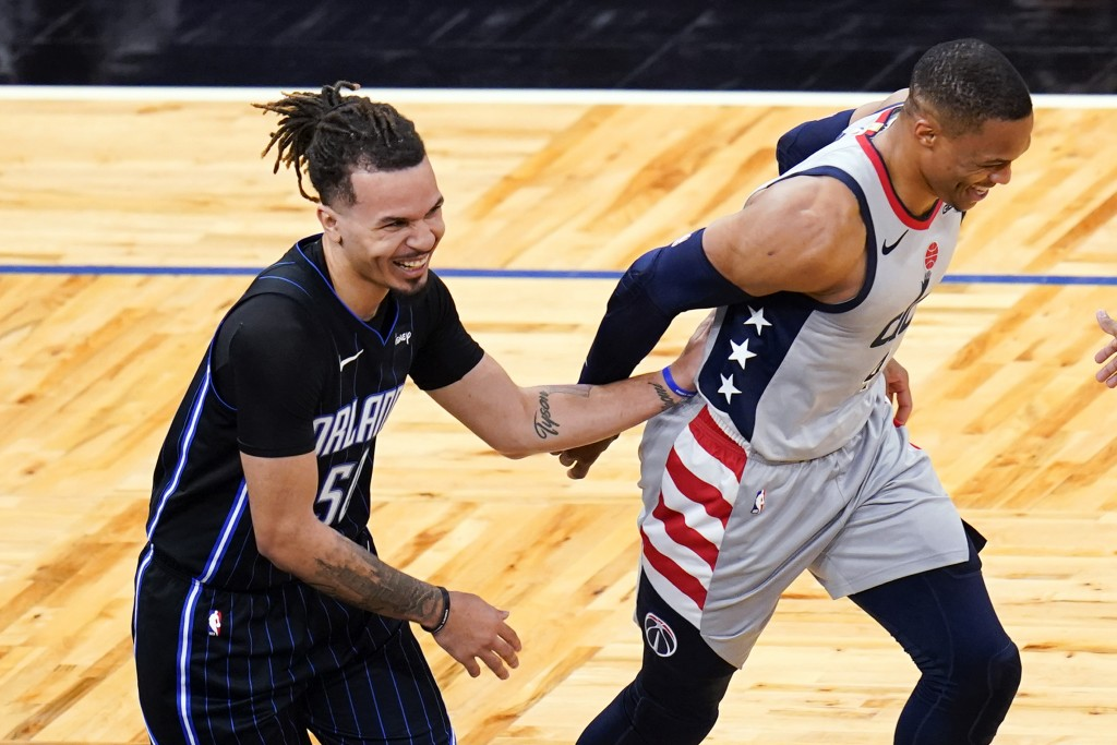 Orlando Magic guard Cole Anthony, left, jokes with Washington Wizards guard Russell Westbrook after Anthony was called for goaltending on a Westbrook ...