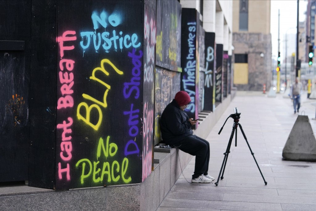A person videotapes across the street from the Hennepin County Government Center, Thursday, April 8, 2021, in Minneapolis where testimony continues in...