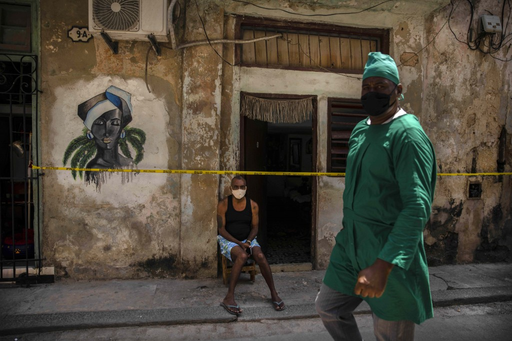 A health worker wearing a mask as a precaution against the spread of the new coronavirus walks in front of a man sitting at the entrance of his quaran...