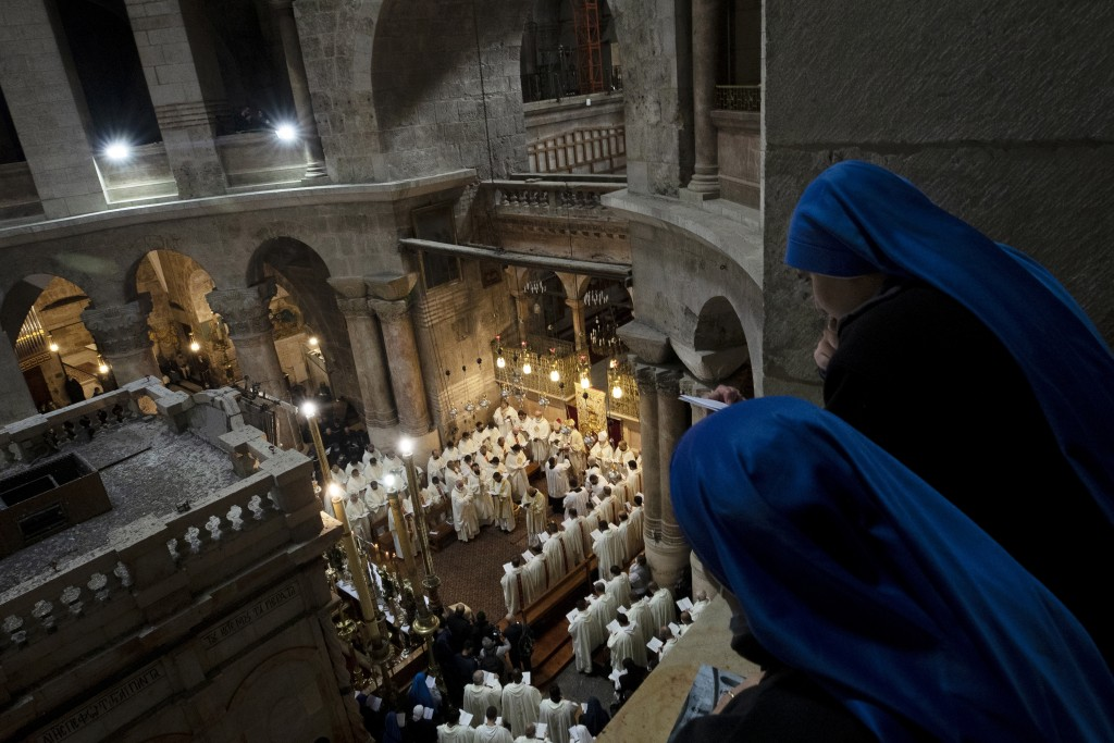 Nuns watch Holy Thursday mass led by the Latin Patriarch at the Holy Sepulchre, traditionally where many Christians believe Jesus Christ was crucified...