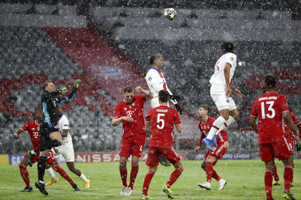 PSG's Marquinhos, right, and his teammate Kylian Mbappe jump for the ball as Bayern's players defend during the Champions League quarterfinal soccer m...
