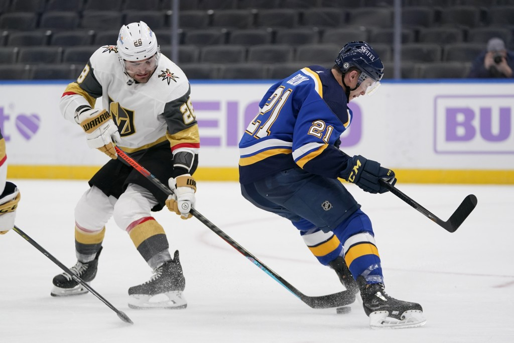 Vegas Golden Knights' William Carrier (28) reaches for the puck as St. Louis Blues' Tyler Bozak (21) skates past during the second period of an NHL ho...
