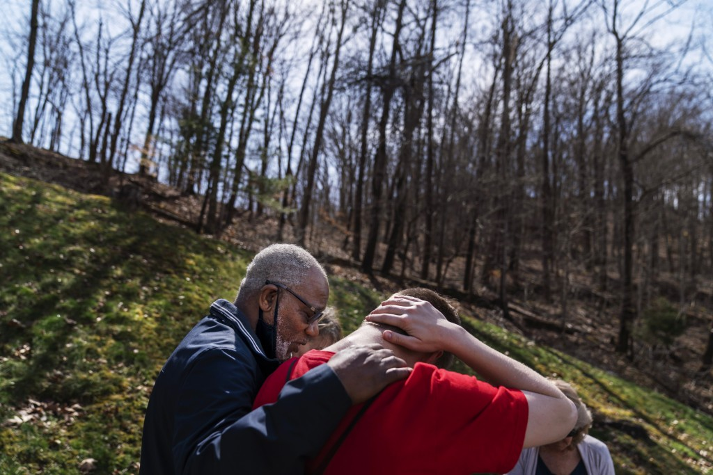 Quick Response Team member pastor Fred McCarty, prays with a young man who recently overdosed as they visit him at his home in Barboursville, W.Va., T...
