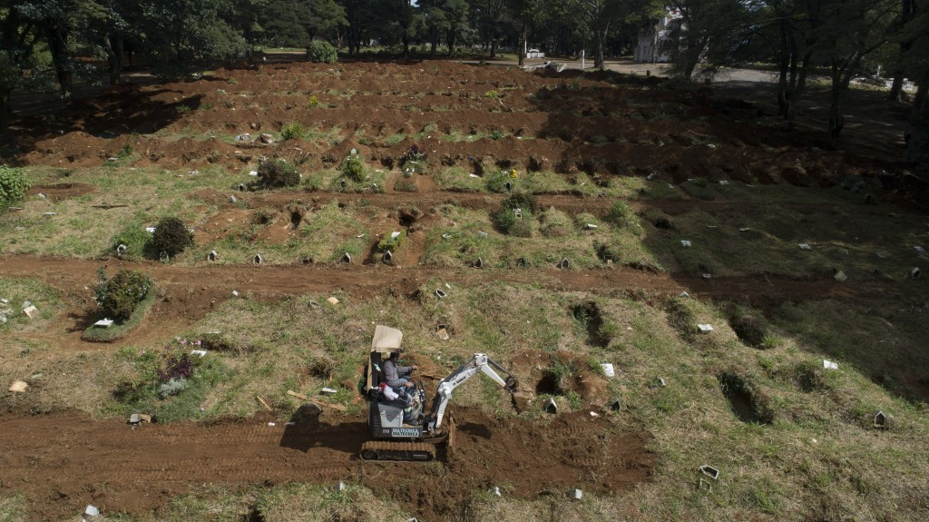 A worker digs more graves at the Vila Formosa cemetery amid the COVID-19 pandemic in Sao Paulo, Brazil, Wednesday, April 7, 2021. (AP Photo/Andre Penn...