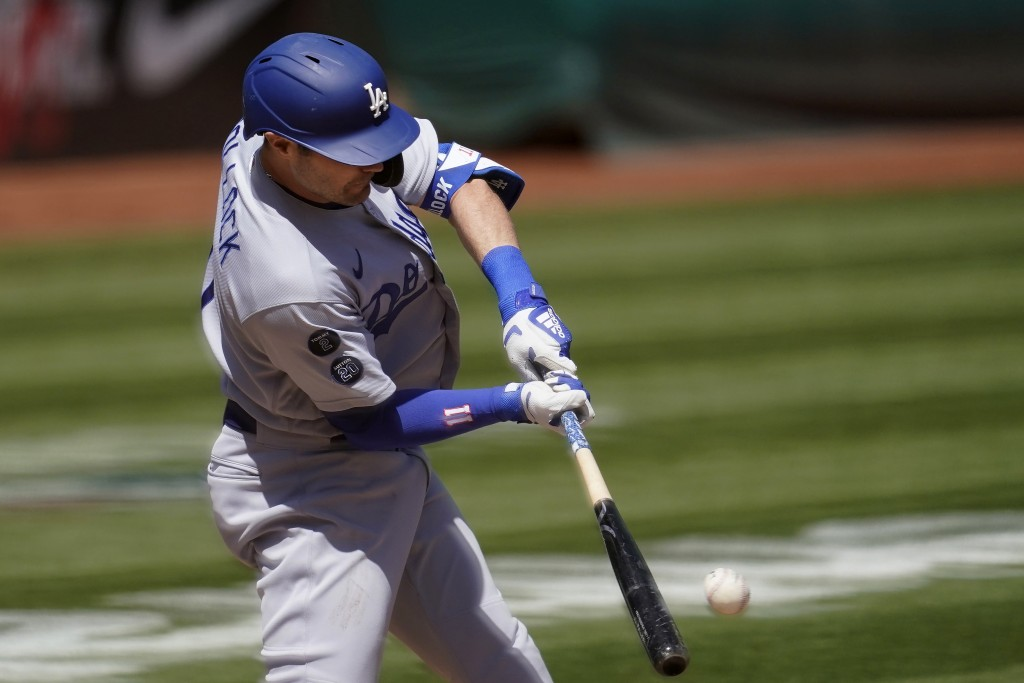 Los Angeles Dodgers' A.J. Pollock hits a run-scoring single against the Oakland Athletics during the first inning of a baseball game in Oakland, Calif...
