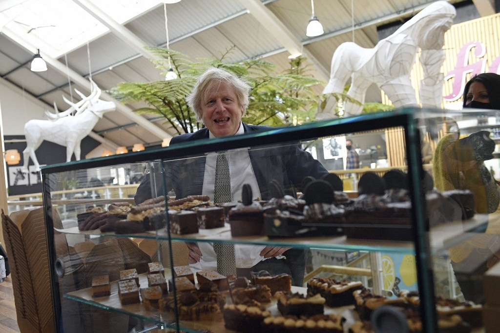 Britain's Prime Minister Boris Johnson looks at a display of cakes and desserts during a visit to Lemon Street Market in Truro, England, Wednesday, Ap...