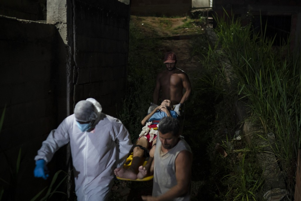Mobile Emergency Care Service (SAMU) worker Sergio Ricardo, left, and two neighbors, carry an elderly COVID-19 patient to an ambulance in Duque de Cax...