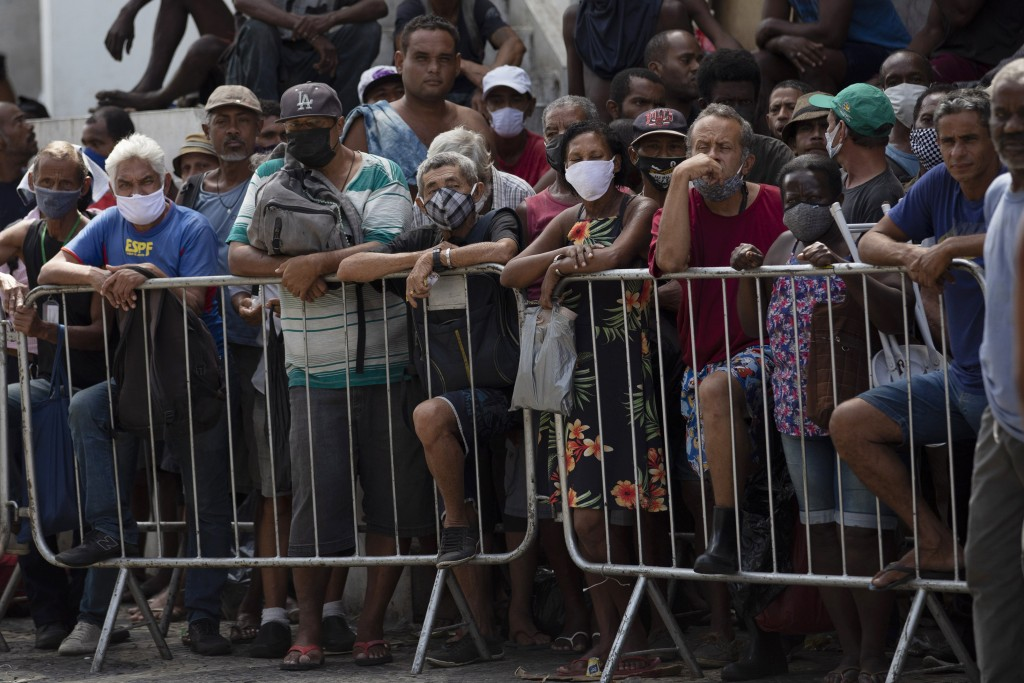 People wait in line for a meal donated by the Leao Xlll Foundation amid the COVID-19 pandemic in Rio de Janeiro, Brazil, Wednesday, April 7, 2021. (AP...