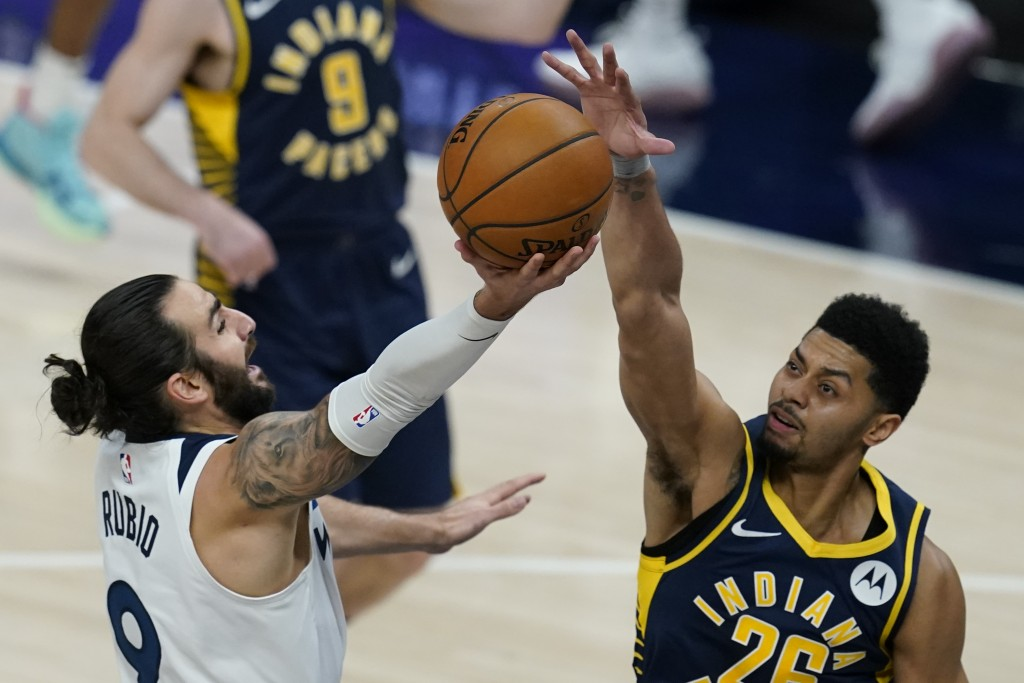 Minnesota Timberwolves' Ricky Rubio (9) has his shot blocked by Indiana Pacers' Jeremy Lamb (26) during the first half of an NBA basketball game, Wedn...