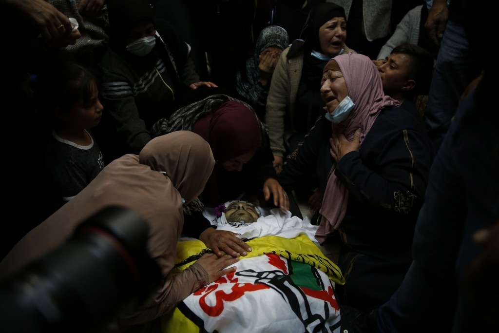 Palestinians carry the body of Osama Mansour during his funeral, in the village of Biddu near the West Bank city of Ramallah, Tuesday, April 6, 2021. ...