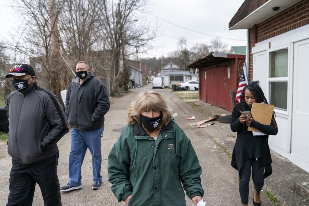 Sue Howland, center, walks down a street to check on someone who overdosed days before with fellow members of the the Quick Response Team, from left, ...