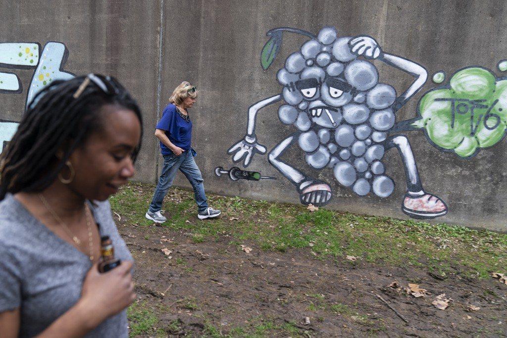 Larrecsa Cox, foreground, and Sue Howland with the Quick Response Team, walk past addiction-themed graffiti near a tent encampment along the river loo...