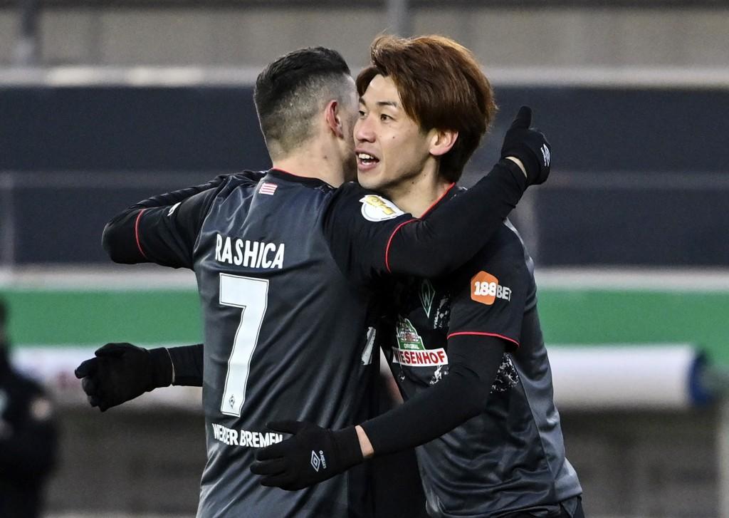 Bremen's Yuya Osako, right, celebrates with teammate Milot Rashica after scoring during the German soccer cup quarter final soccer match between Jahn ...