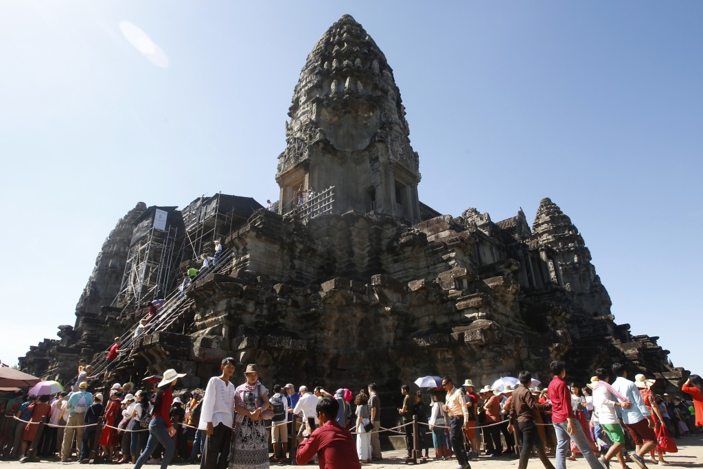 FILE - In this Sunday, Dec. 31, 2017, file photo, tourists line up for stepping up Angkor Wat temple outside Siem Reap, Cambodia. Cambodia is closing ...