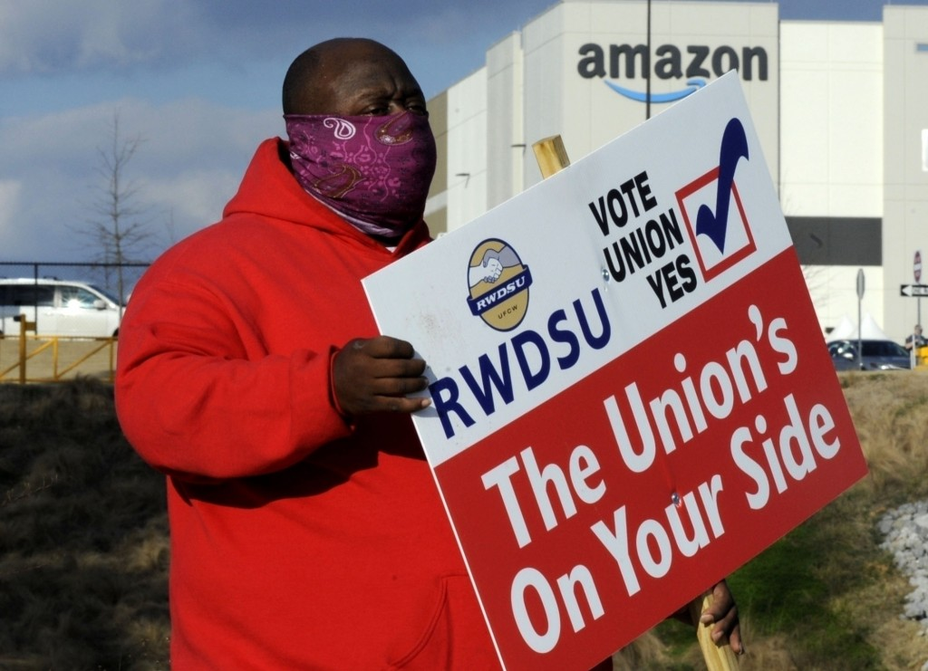 FILE - In this Tuesday, Feb. 9, 2021, file photo, Michael Foster of the Retail, Wholesale and Department Store Union holds a sign outside an Amazon fa...