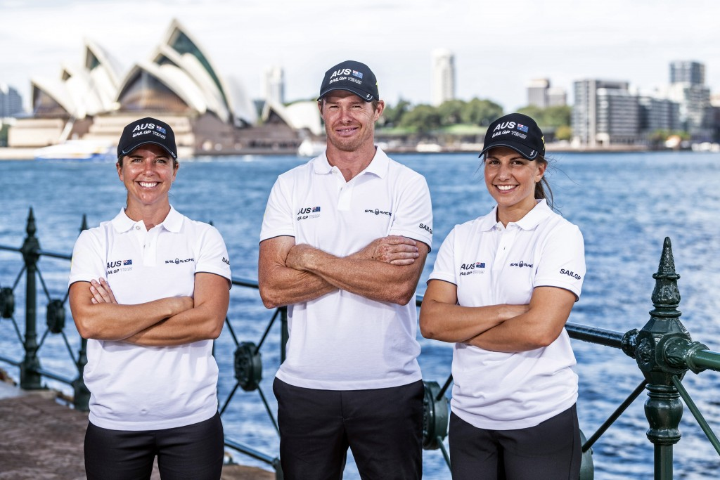 In this photo provided by Sail GP are Nina Curtis, left, and Lisa Darmanin, right, posing with helmsman and CEO Tom Slingsby at Sydney Harbour Wednesd...