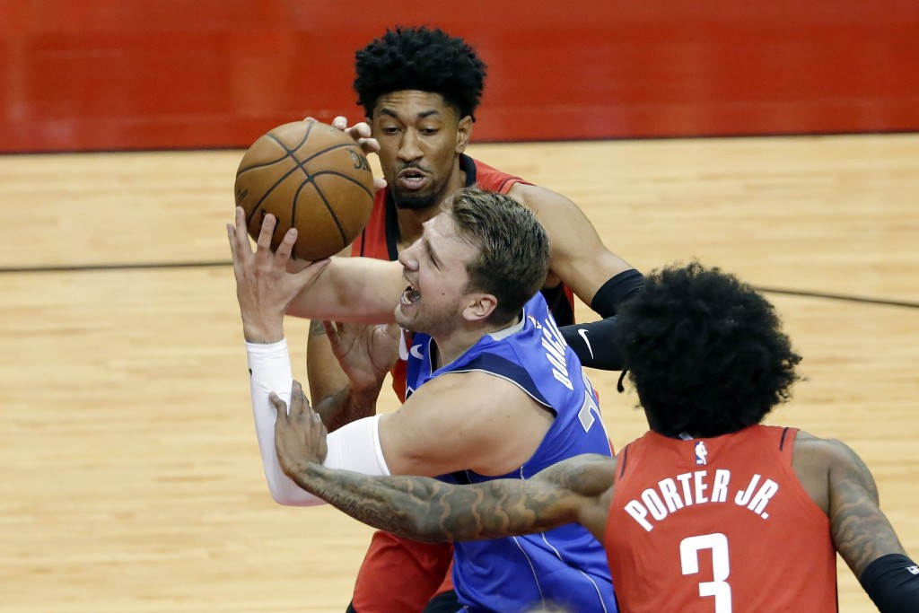 Dallas Mavericks guard Luka Doncic (77) is fouled as he drives to the basket between during the first half of an NBA basketball game Wednesday, April ...
