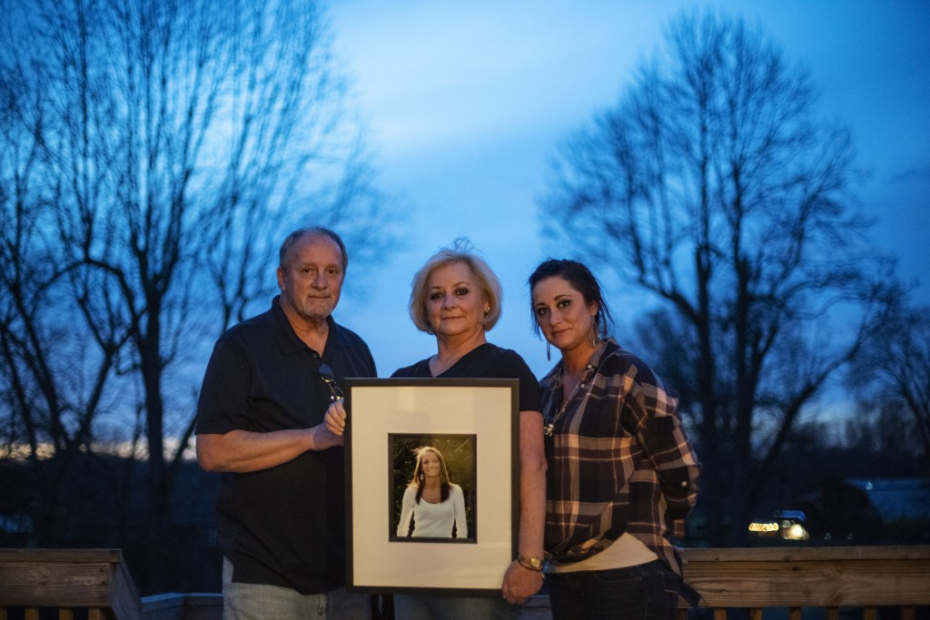 Jeff and Lola Carter stand with their daughter, Amanda, and a framed photo of Kayla, their daughter who struggled with drug addiction, Tuesday, March ...