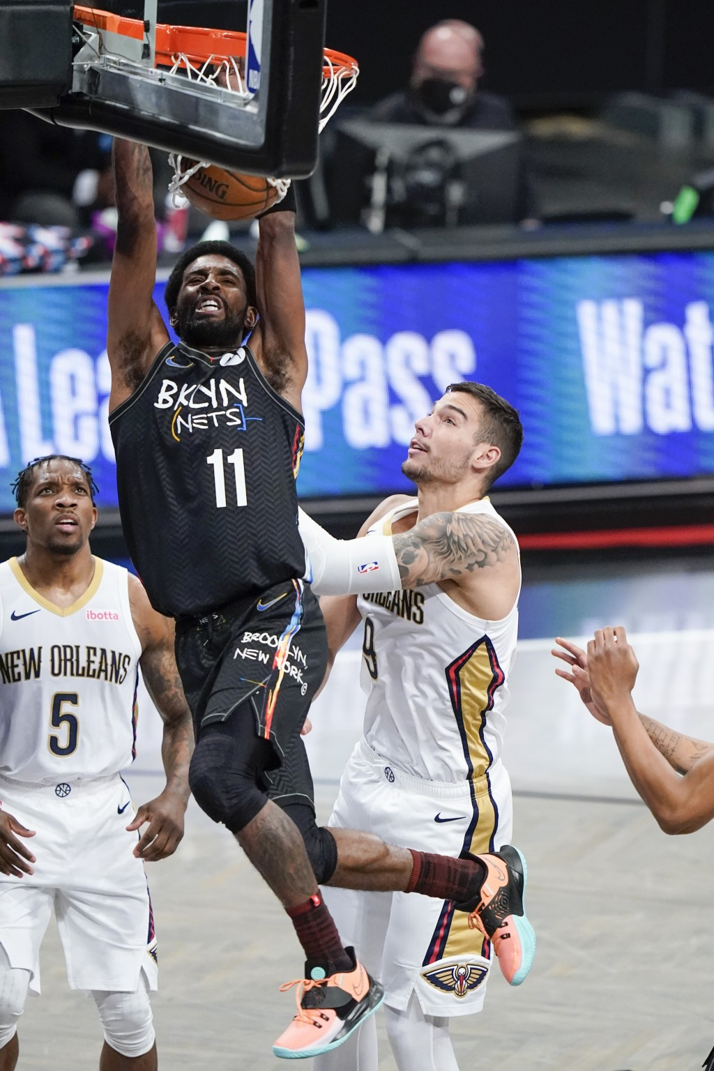 Brooklyn Nets' Kyrie Irving (11) dunks the ball in front of New Orleans Pelicans' Eric Bledsoe (5) and Willy Hernangomez (9) during the first half of ...