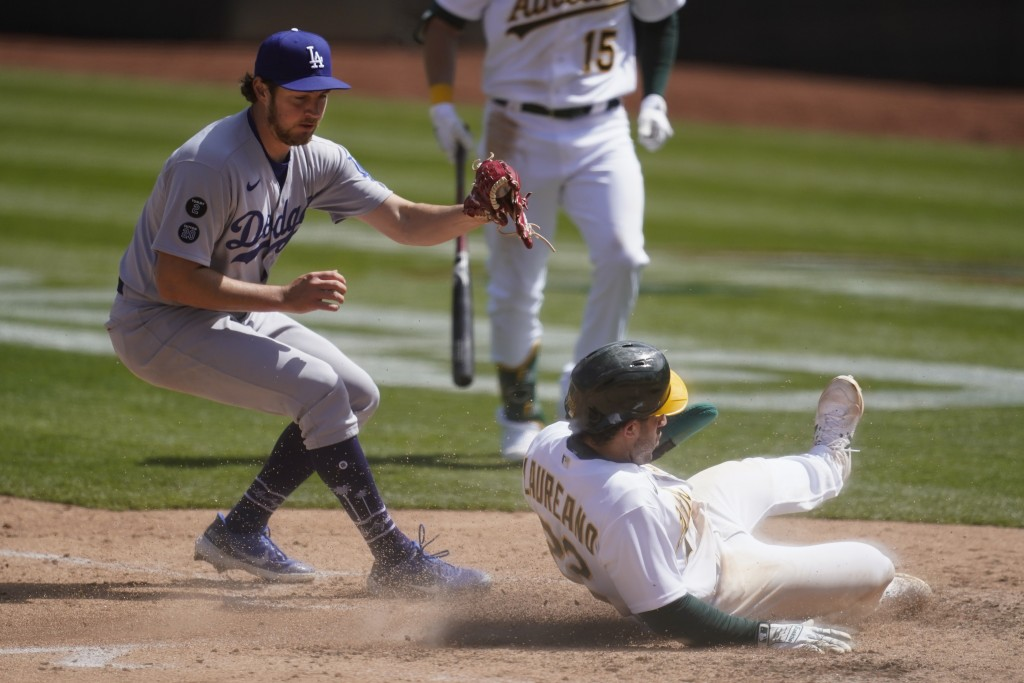 Oakland Athletics' Ramon Laureano, bottom right, slides home to score past Los Angeles Dodgers starting pitcher Trevor Bauer during the fourth inning ...