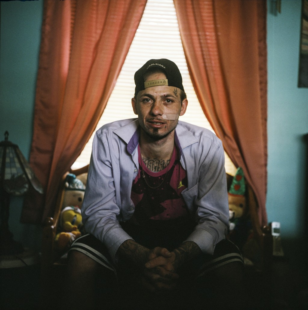 In this photo made with a medium format film camera, Joshua Messer, 29, sits for a portrait in his aunt's home where he's currently staying, days afte...