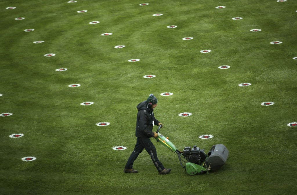 A member of the grounds staff cuts the grass dotted with social distance markers in the parade ring before the start of the Liverpool NHS Day of the 2...