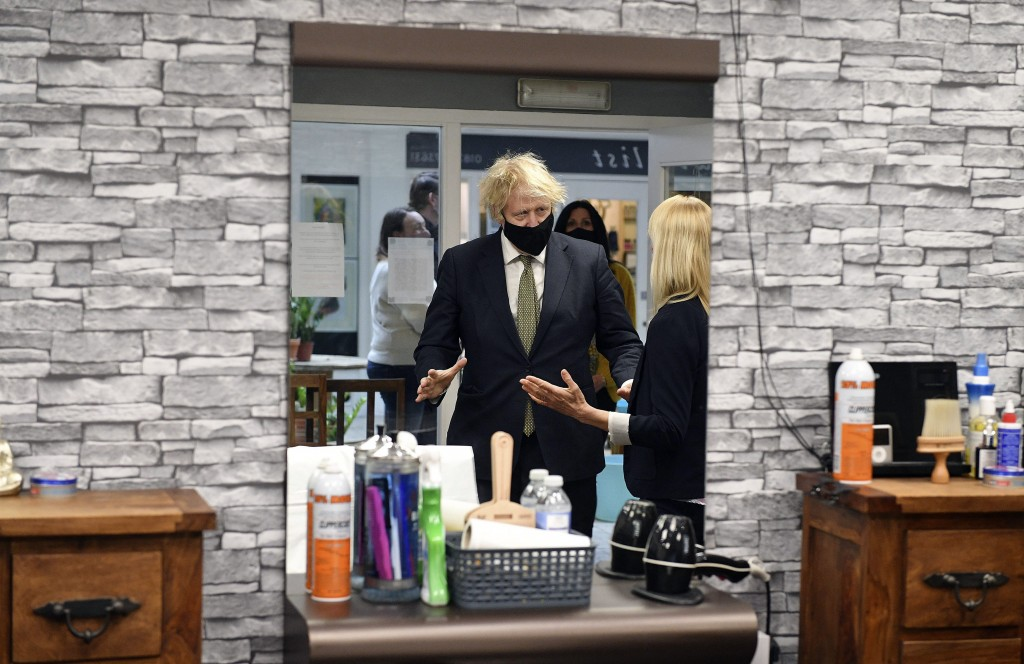 Britain's Prime Minister Boris Johnson in Lemonheads Barber shop during a visit to Lemon Street Market in Truro, England, Wednesday, April 7, 2021  to...