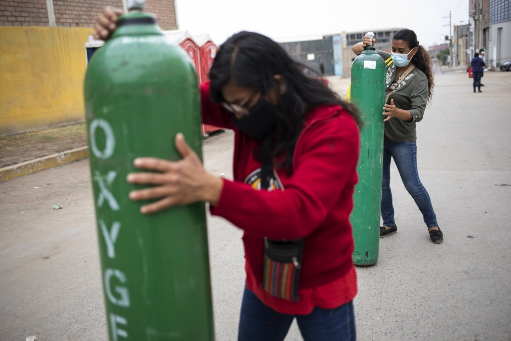 Marlene and Rosalyn Del Aguila roll tanks filled with oxygen to a waiting car, to deliver to their mother who has tested positive for COVID-19, in the...