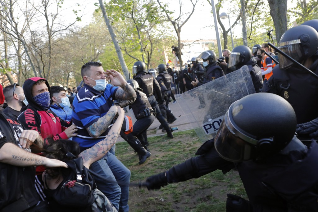 Spanish police use batons to keep protesters away from supporters of the far-right Vox party during a party rally in Madrid's Vallecas neigborhood, a ...