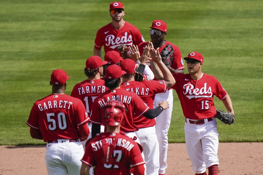 Cincinnati Reds' teammates celebrate after defeating the Pittsburgh Pirates 11-4 at Great American Ball Park in Cincinnati, Wednesday, April 7, 2021. ...