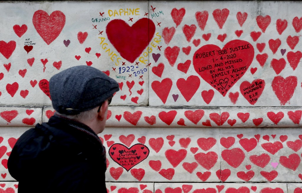 A man walks past the National Covid Memorial Wall commemorating all those who have died of coronavirus, on the Thames Embankment opposite the Houses o...