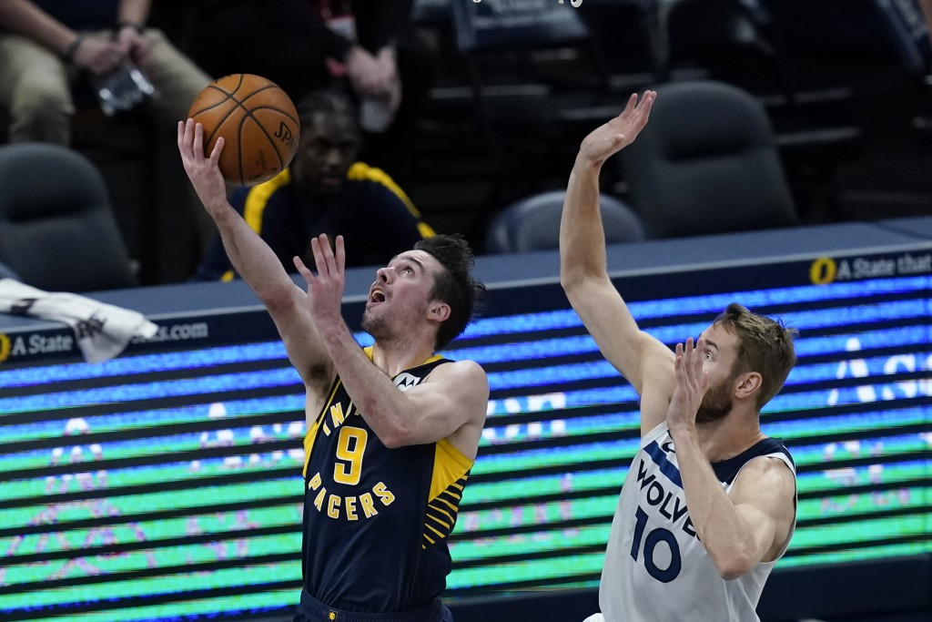 Indiana Pacers' T.J. McConnell (9) puts up a shot against Minnesota Timberwolves' Jake Layman (10) during the first half of an NBA basketball game, We...