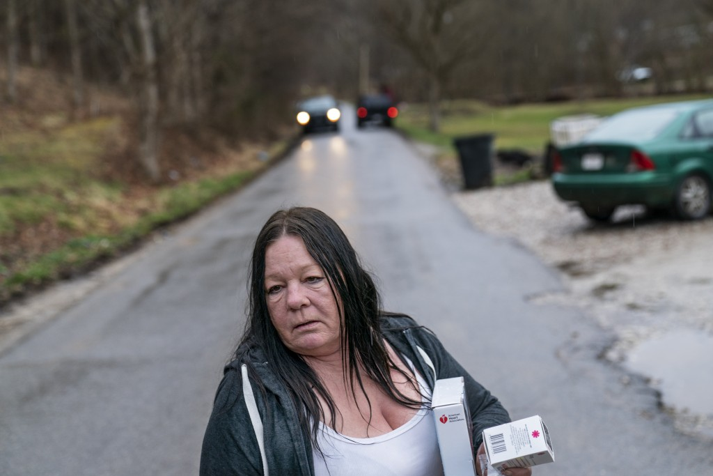 Yvonne Ash carries back to her house a CPR kit and a supply of the overdose reversal medication naloxone after a visit from the Quick Response team, w...