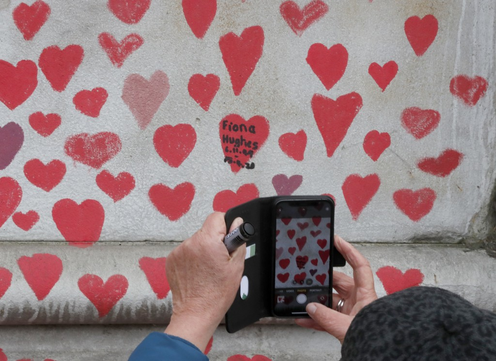 A woman takes a picture on her phone as people paint red hearts marking the completion of the approximately 150,000 hearts being painted onto the Nati...