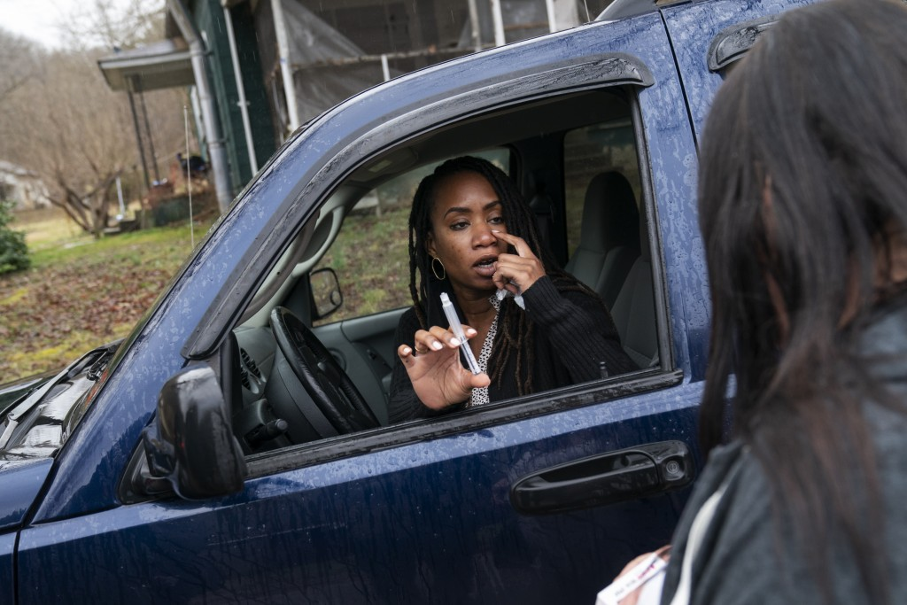 Larrecsa Cox, who leads the Quick Response Team, demonstrates to Yvonne Ash outside her home in Branchland, W.Va., Monday, March 15, 2021, how to admi...