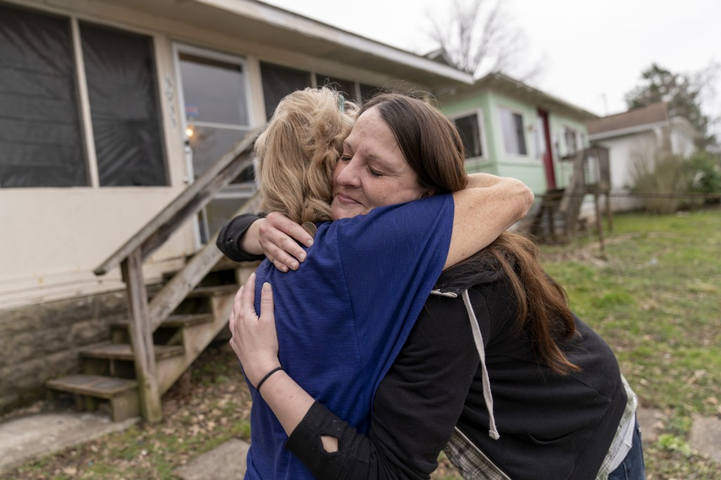 Sarah Kelly, right, is embraced by Sue Howland, with the Quick Response Team, after Howland presented her with a coin marking Kelly's one-year anniver...