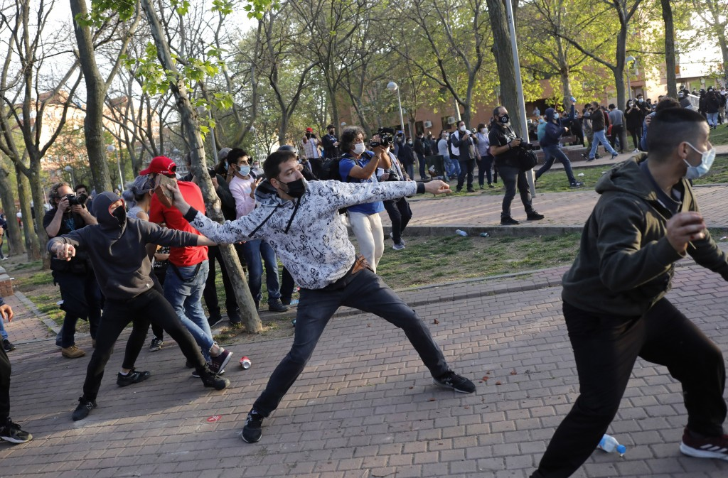 Protesters throw stones at far-right Vox supporters during a party rally in Madrid's Vallecas neigborhood, a traditional left-wing bastion, Spain, Wed...