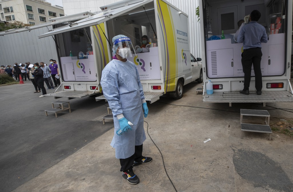 A health worker prepares to collect nasal swab sample from a worker at a local entertainment venue site where a new cluster of COVID-19 infections wer...