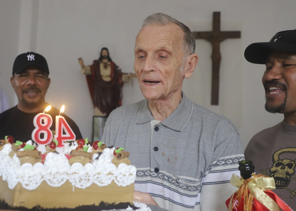Now-defrocked Catholic priest Richard Daschbach, center, is presented a cake during his 84th birthday in Dili, East Timor, on Tuesday, Jan. 26, 2021. ...