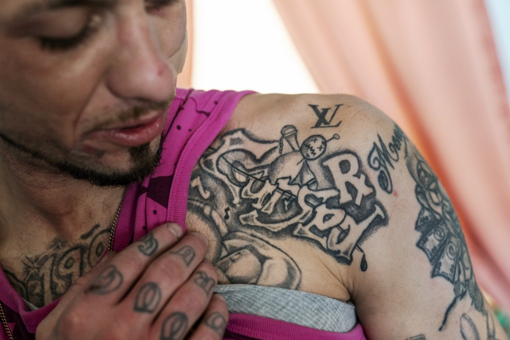Joshua Messer, 29, shows off a tattoo he got in prison, Tuesday, March 16, 2021, while staying at his aunt's house just days after overdosing in Hunti...