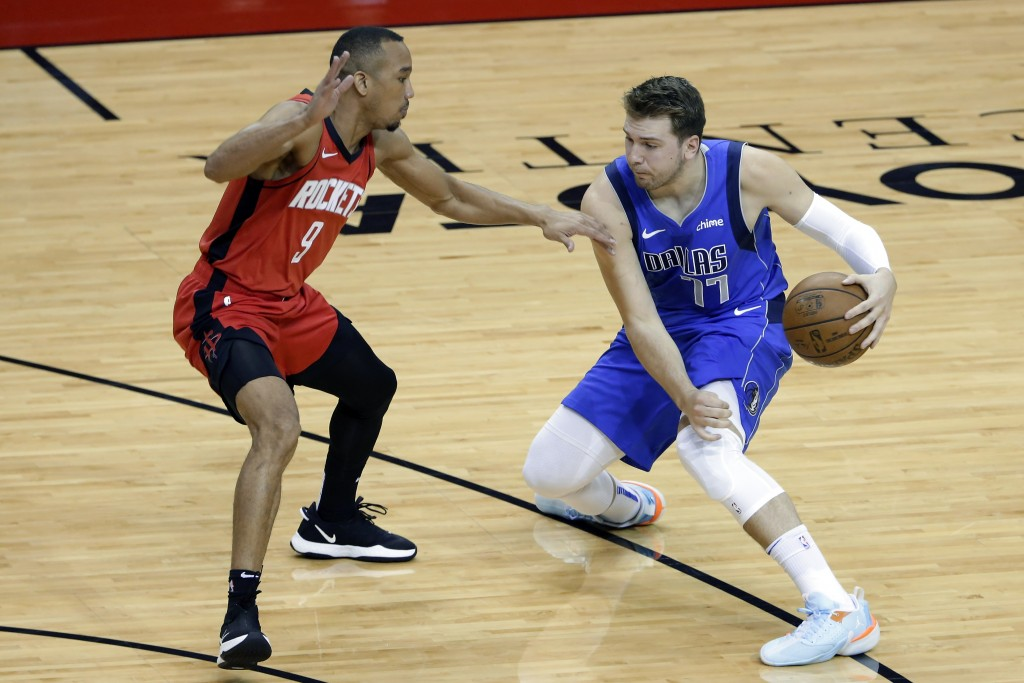 Dallas Mavericks guard Luka Doncic (77) works to drive around Houston Rockets guard Avery Bradley (9) during the first half of an NBA basketball game ...