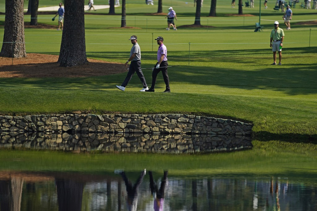Bubba Watson, left, and Webb Simpson walk along the 15th fairway during a practice round for the Masters golf tournament on Wednesday, April 7, 2021, ...