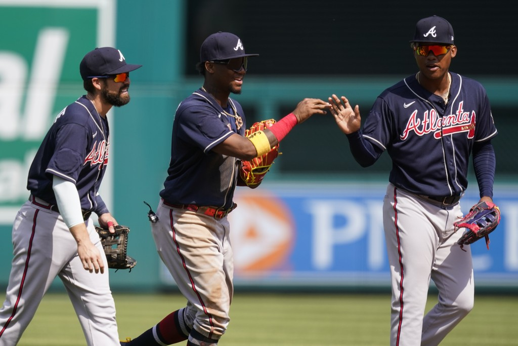 Atlanta Braves outfielders Ender Inciarte, left, Ronald Acuna Jr., and Marcell Ozuna celebrate after the first baseball game of a doubleheader at Nati...