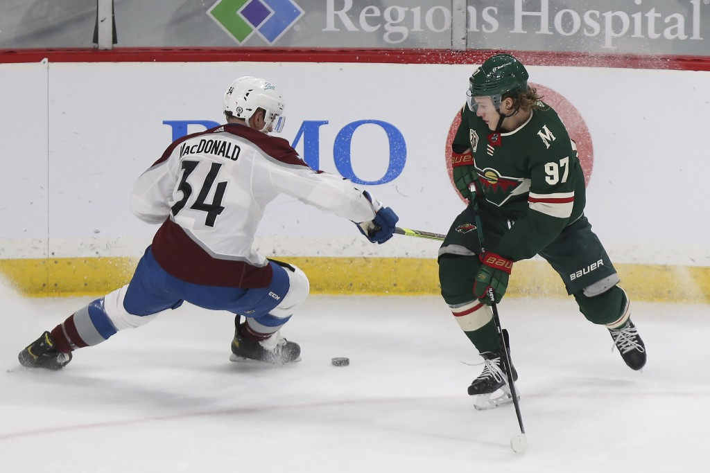Minnesota Wild's Kirill Kaprizov (97) and Colorado Avalanche's Jacob MacDonald (34) go after the puck during the first period of an NHL hockey game We...