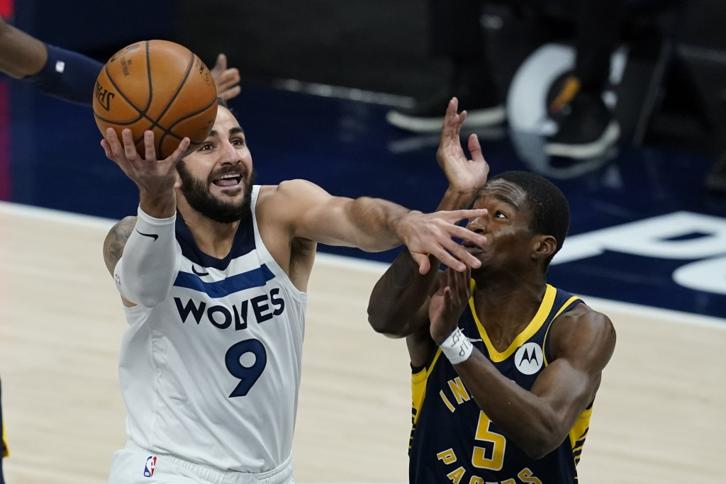 Minnesota Timberwolves' Ricky Rubio (9) goes to the basket against Indiana Pacers' Edmond Sumner (5) during the first half of an NBA basketball game, ...