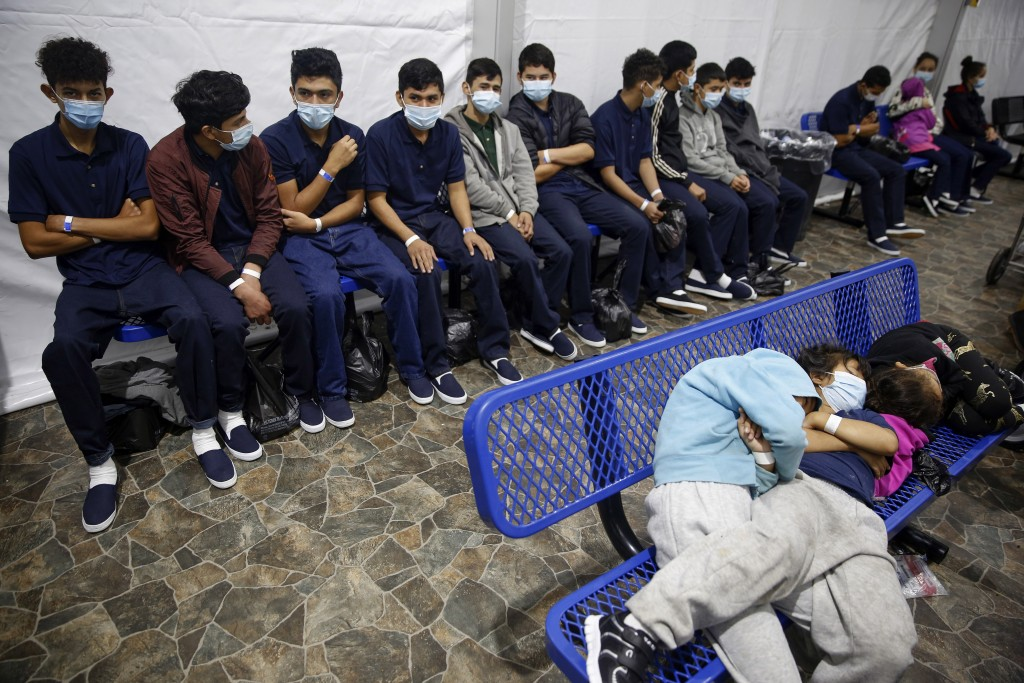 FILE - In this March 30, 2021, file photo, young unaccompanied migrants wait for their turn at the secondary processing station inside the U.S. Custom...