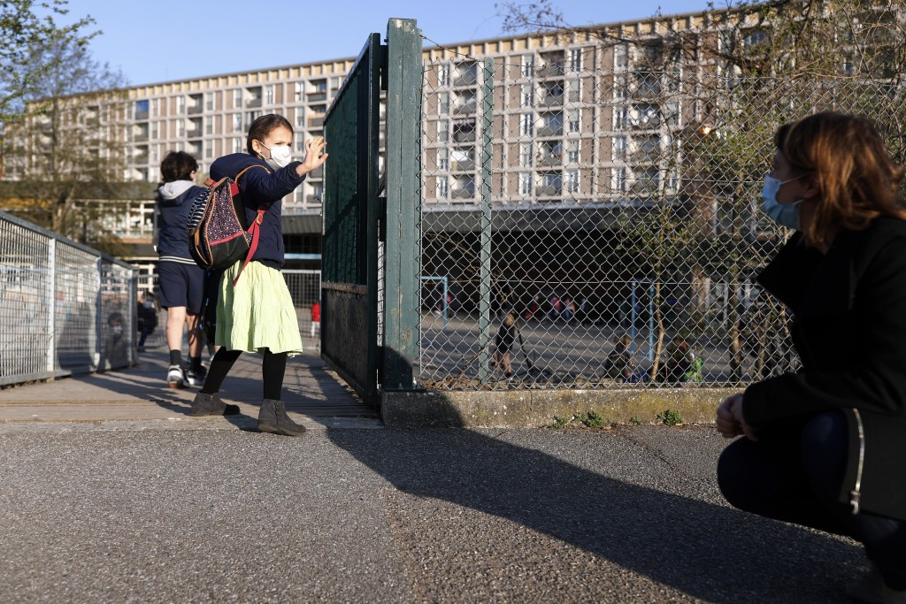 FILE - In this Thursday, April 1, 2021 file photo, Emma Woodroof waves goodbye to her mother Julie as she enters her school in Strasbourg, eastern Fra...
