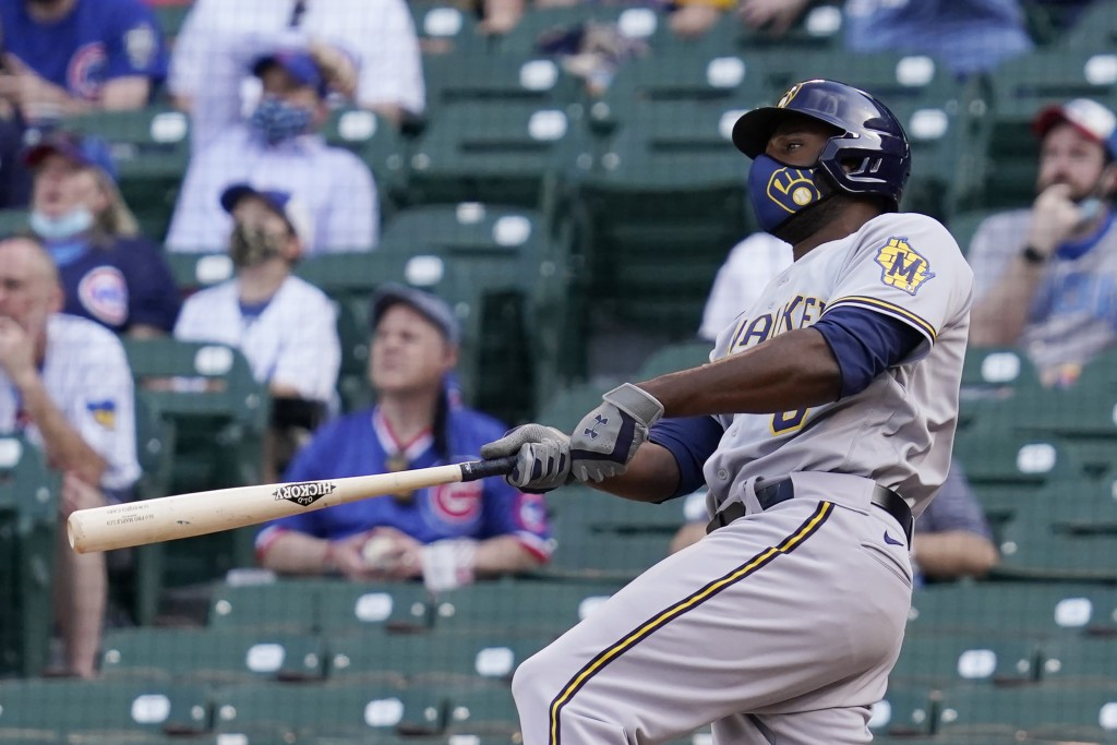 Milwaukee Brewers' Lorenzo Cain watches after hitting a three-run home run against the Chicago Cubs during the 10th inning of a baseball game in Chica...