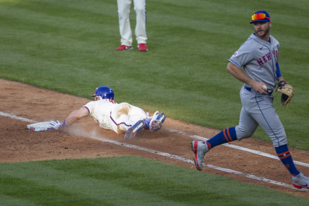 Philadelphia Phillies' Bryce Harper slides into first base on a bunt before New York Mets first baseman Pete Alonso could make the tag during the fift...