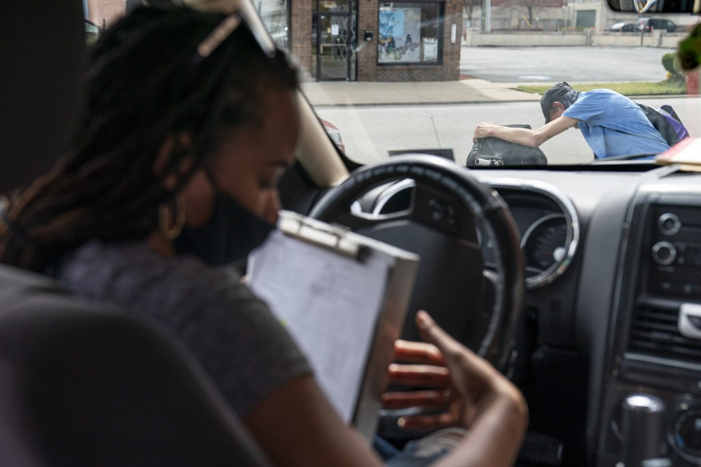 Larrecsa Cox, who leads the Quick Response Team, sits in her car with a list of people to visit after giving a man on the street a supply of the overd...